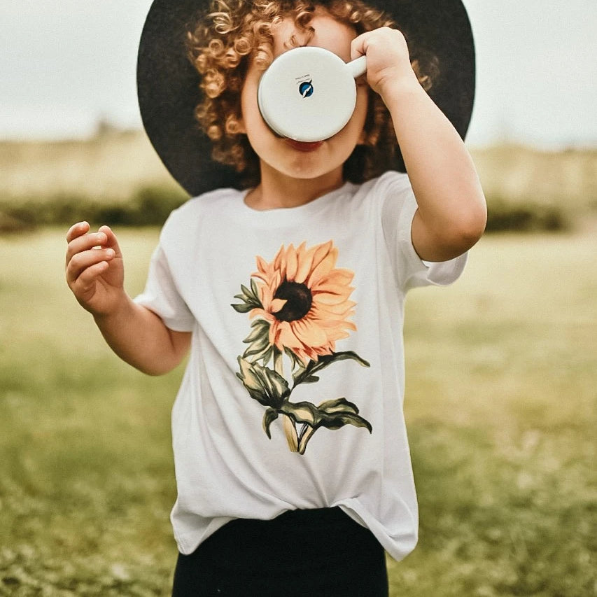 toddler wearing a white tee shirt with a sunflower on it
