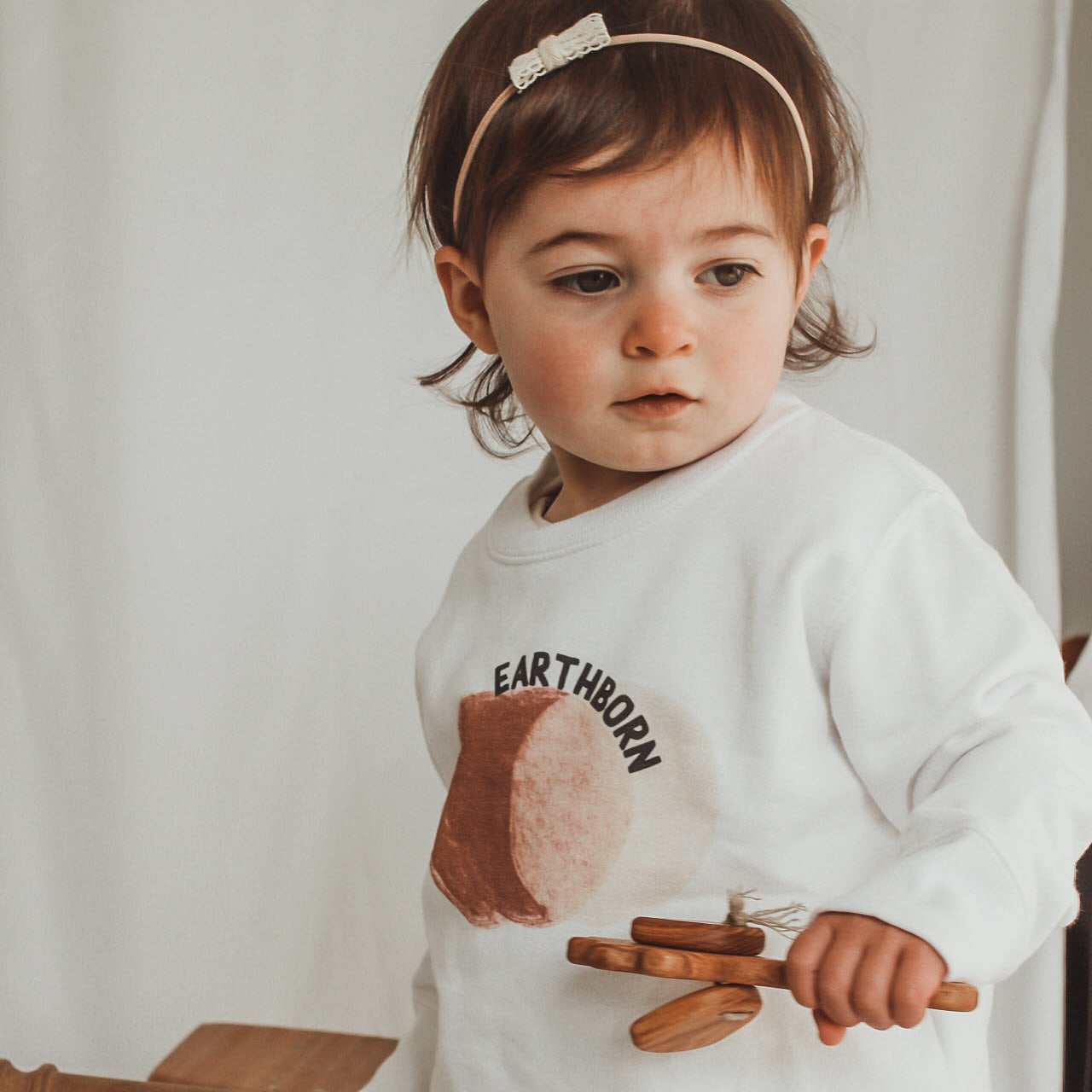 Toddler girl holding a wooden rattle and wearing a white sweatshirt printed with neutral colored circles and the word Earthborn