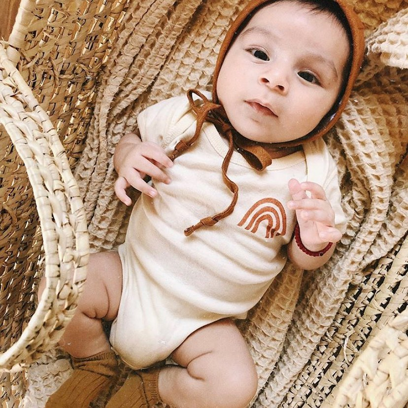 baby wearing a white bodysuit with a small orange rainbow on it