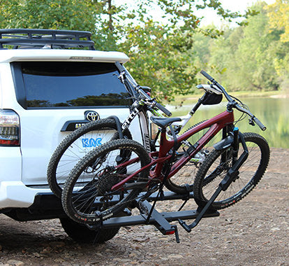 A white Toyota 4Runner is parked by the water with a KAC C2 Hitch Mounted bike rack folded flush against the back of the car. A bicycle and campfire sit nearby.