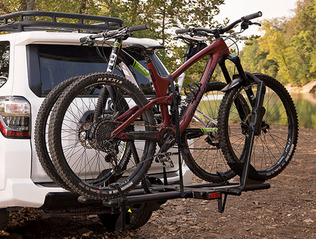 KAC C2 Premium Hitch Mounted Bike Rack loaded with two bicycles on the back of a white Toyota 4Runner parked on a gravel bar.