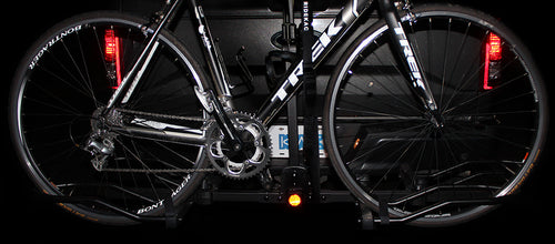 close up image of a road bike loaded on a K2 Overdrive Sports bike rack in the dark with safety reflectors activated