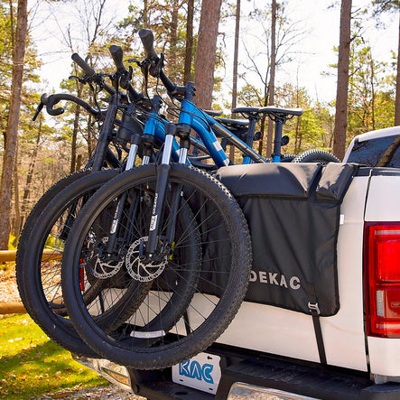 Large tailgate pad cover on a white pickup truck carrying four bicycles