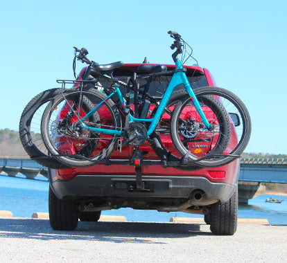 jeep grand cherokee parked by a lake with KAC K2-RT bike rack mounted on car hitch with electric bikes loaded