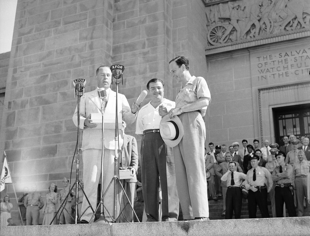 Comedians Bud Abbott and Lou Costello receive an ear of corn from Governor Dwight Griswold on the north steps of the State Capitol Building, July 31, 1942. -- Courtesy Nebraska State Historical Society / #RG2183.PH001942-000731-3