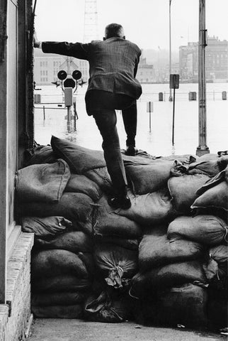 Man standing on sandbags during extensive flooding, 1965. -- Quad-City Times