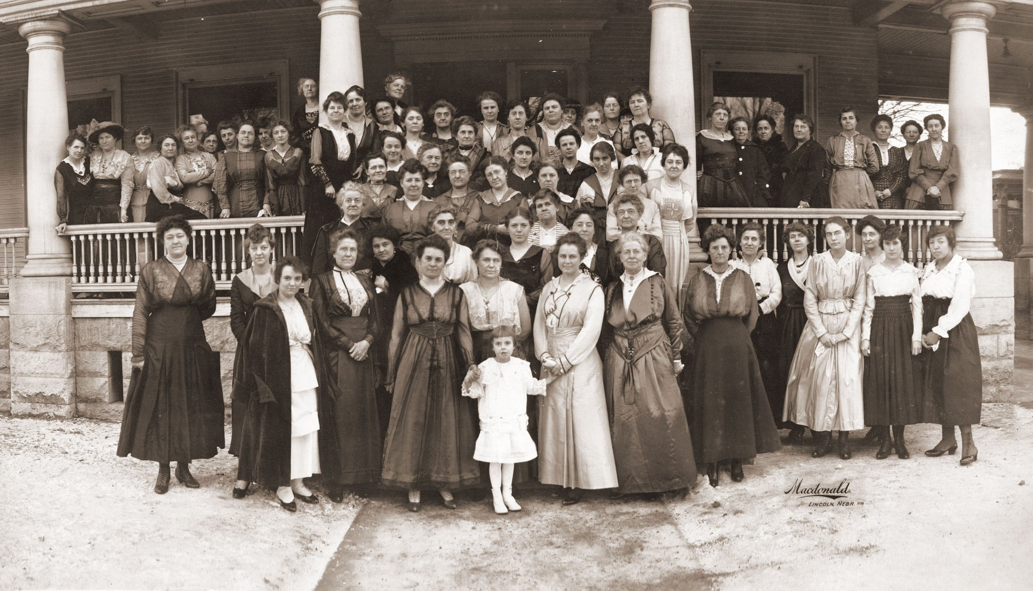 Nebraska Legislative Ladies League in front of the Governor's mansion, Lincoln, 1917. Gov. Keith Neville was Governor from 1917 to 1919. In this photo, Mrs. Neville was taking over as honorary president from Mrs. Morehead. The little girl in front is Mary Nelson Neville. -- Courtesy Nebraska State Historical Society