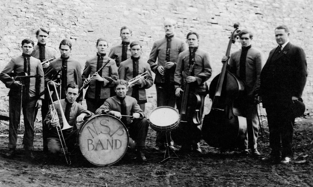 The 11-piece Nebraska State Penitentiary Band, circa 1918. All band members were inmates serving time. William T. Fulton, the warden, stands on the right holding a bowler hat. -- Nebraska State Historical Society