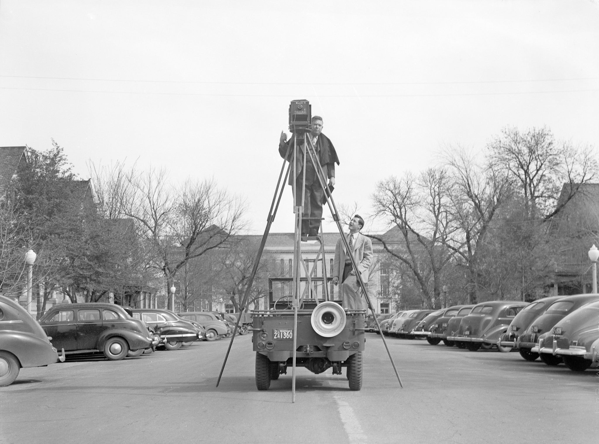 "A photographer uses a large tripod to take photographs from back of a jeep on 13th & ""Q"" Streets, April 15, 1946. -- Nebraska State Historical Society"