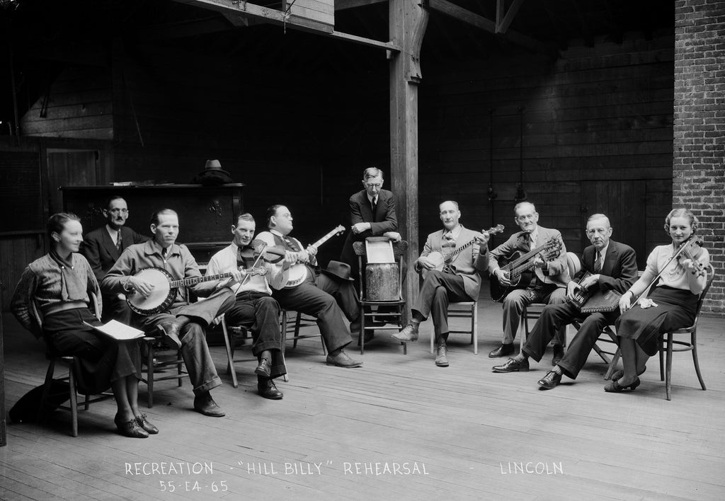 "A FERA ""Hill Billy"" orchestra practices at Randolph School, circa 1935. Among the instruments used are fiddles, guitars, banjos, and a washboard. It is led by assistant supervisor, Montgomery ""Skip"" Dean. -- Nebraska State Historical Society"
