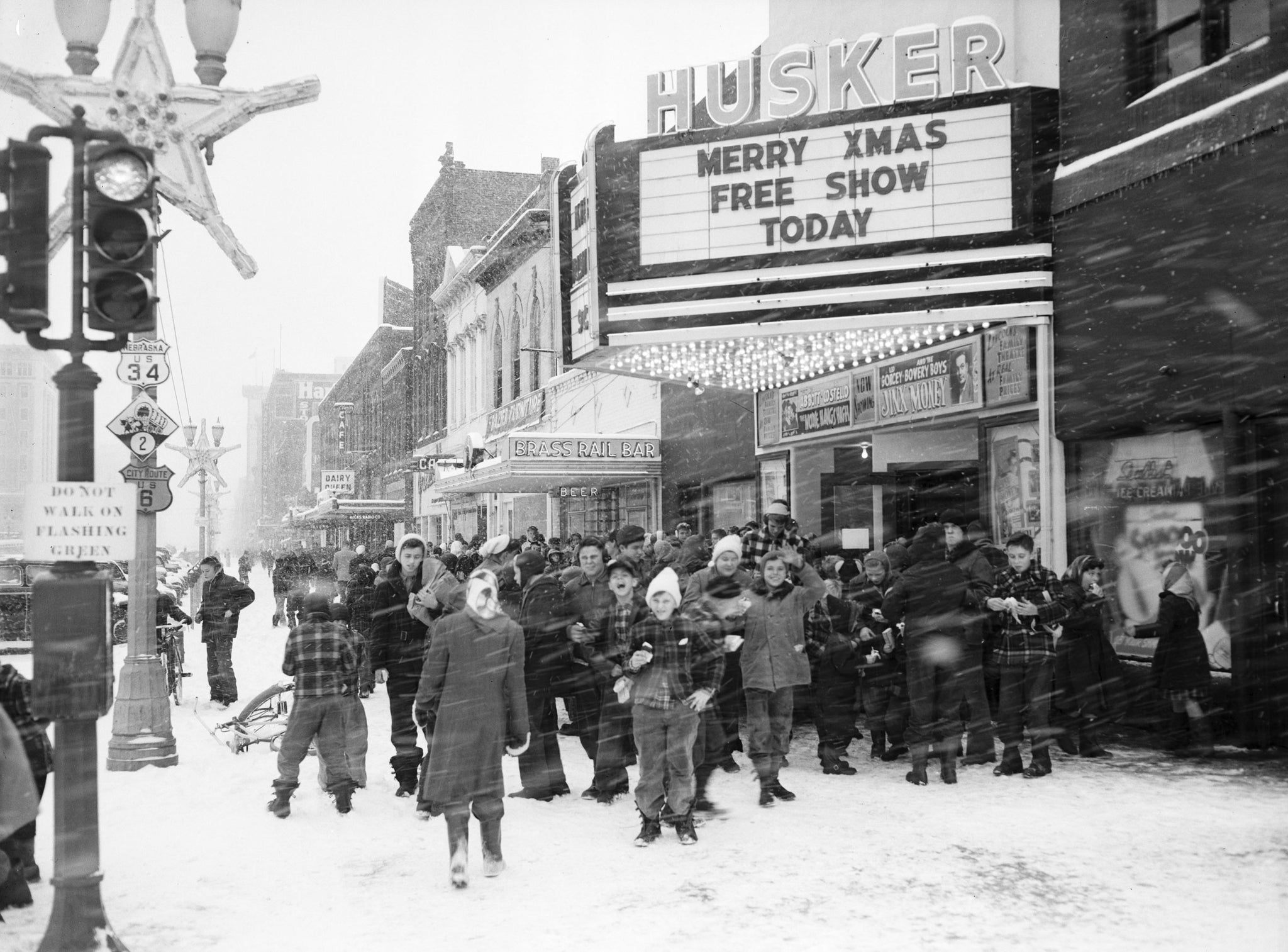 A group of children in front of the Husker Theater, located at 1444 O Street, on Christmas Eve, 1948. -- NEBRASKA STATE HISTORICAL SOCIETY / #RG2183.PH001948-001224