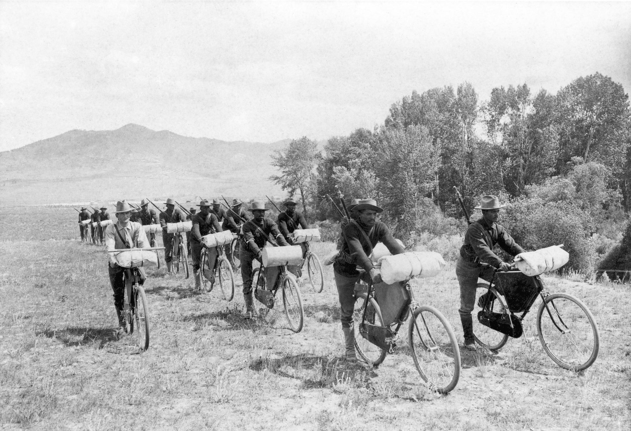 Members of the U.S. Army 25th Infantry Bicycle Corps stationed at Fort Missoula, 1897. Lt. James A. Moss is riding on the left beside the two rows of soldiers. -- Image 73-0031, Courtesy Mansfield Library Archives, University of Montana