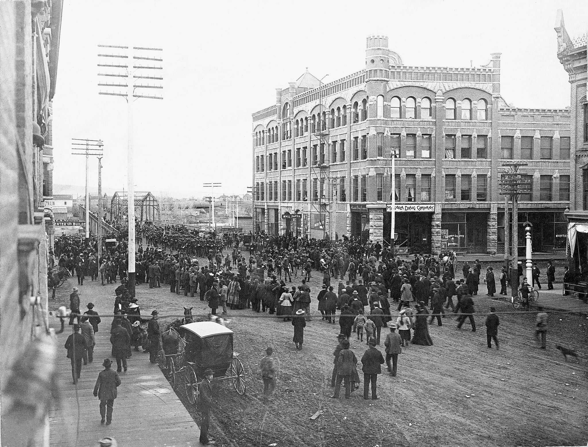 Crowd watching the departure of the United States Army's 25th Infantry across Higgins Bridge in Missoula, April 10, 1898. Headed to Tampa, Florida, they were the first regiment to be active for the Spanish-American War. The Hammond Building is visible in the background. -- Image 76-0200, Courtesy Mansfield Library Archives, University of Montana