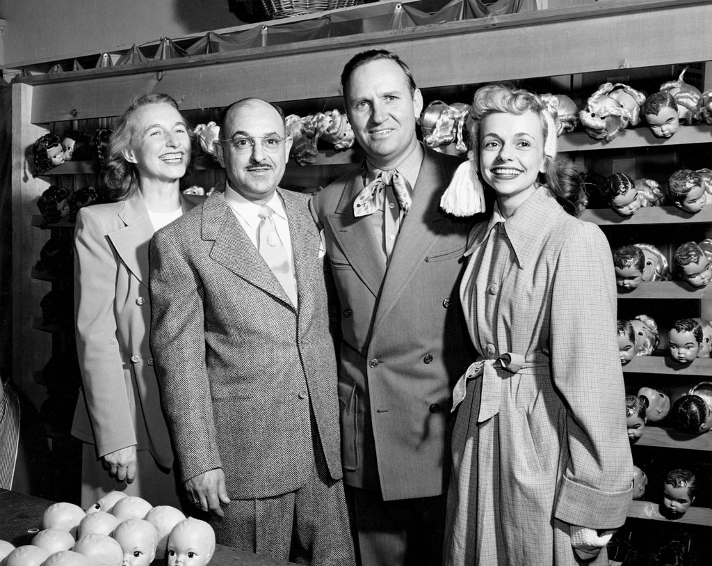 Violet Gradwohl, Harry Gradwohl, Gene Autry, and Terri Lee Schrepel pause for a group photo at the Terri Lee Doll Company factory in Lincoln, circa 1949. -- Courtesy Nebraska State Historical Society / #RG5812.PH0-000042