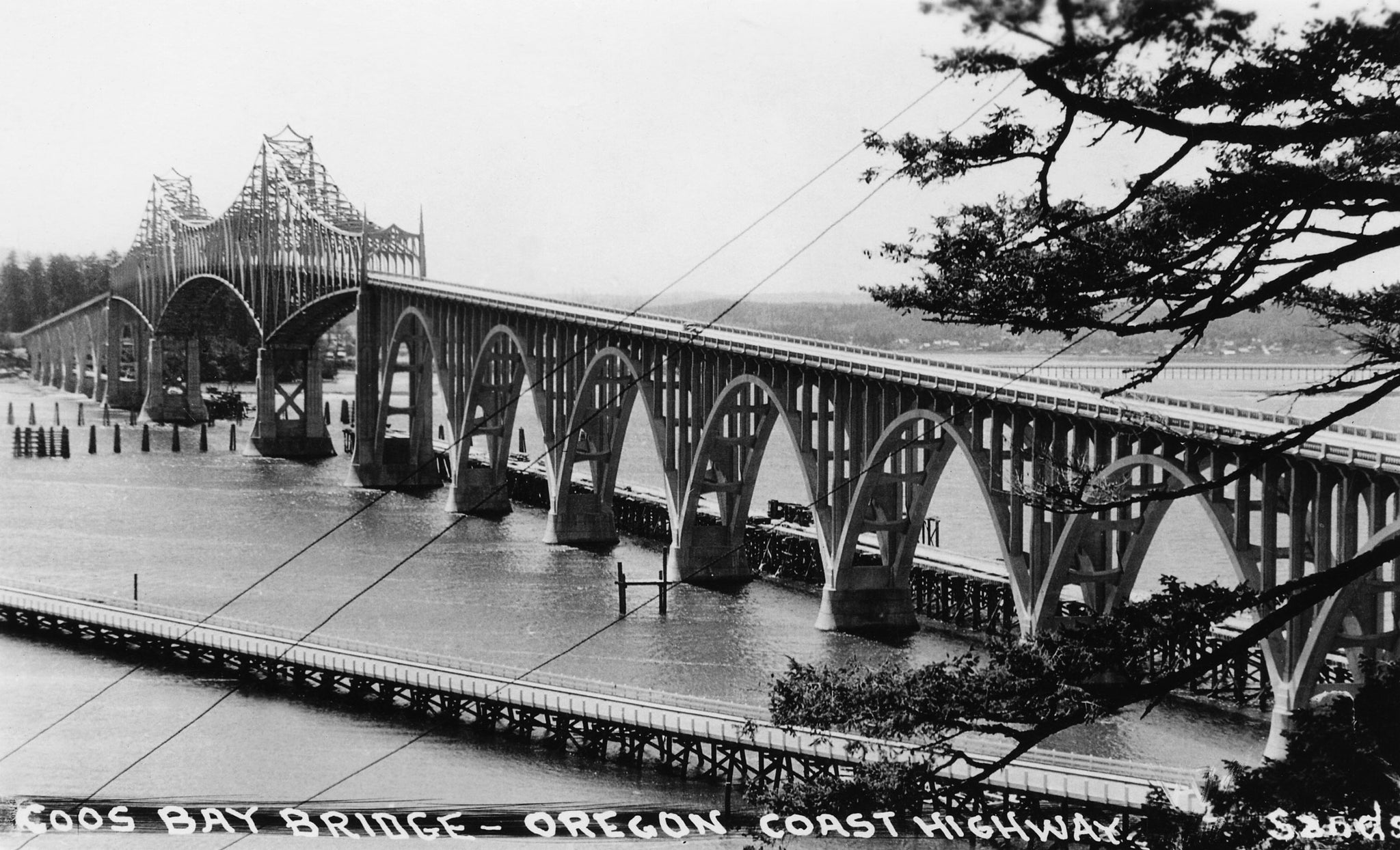 These photos of the completed Coos Bay Bridge in North Bend were both taken from un-mailed and undated postcards from the archives of the Coos History Museum. The photos likely date sometime shortly after completion of the span in 1936. The bridge, extending U.S. Route 101 through North Bend, was renamed the Conde B. McCullough Memorial Bridge in 1947 for its designer. The project was funded largely by the Depression-era Public Works Administration. The bridge was placed on the National Register of Historic Places in 2005. -- COOS HISTORY MUSEUM & MARITIME COLLECTION / 986-14.2