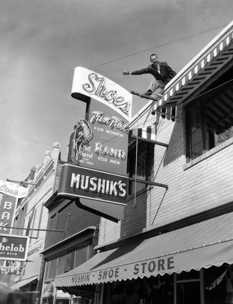 "John Mushik III, on the roof of his store advertising ""Mad"" Market Days, 116 W. Main, Mandan, 1957. During ""Mad"" Market Days, stores would have sidewalk sales and the employees wore crazy costumes. -- Courtesy Becky Mushik Roesler"
