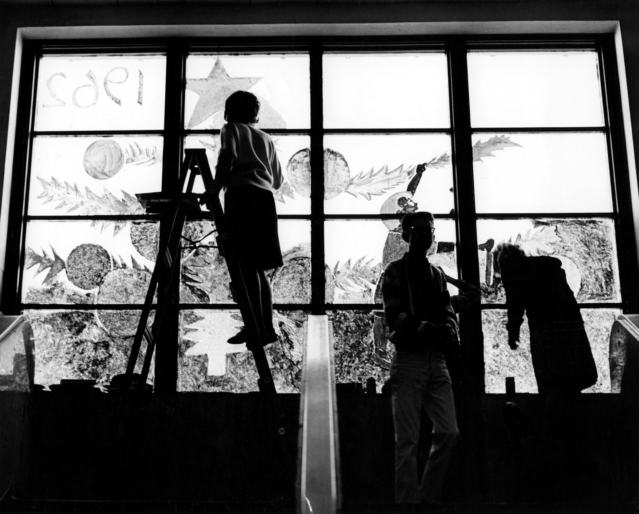 Students at Bismarck High School decorate a classroom window for the Christmas season, December 1962. -- Bismarck Tribune