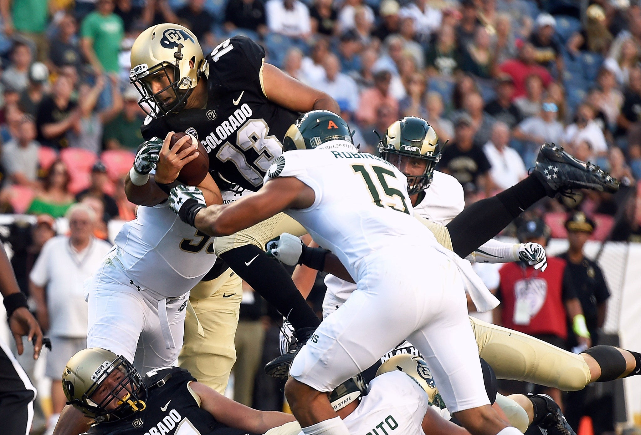 Colorado quarterback Sefo Liufau dives over the line of scrimmage for a touchdown in the first quarter. -- Jeremy Papasso