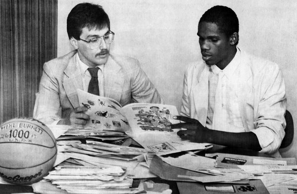 MASH head basketball coach Norm Price helping standout player Mike Burnett review the stacks of college recruiting materials that came in for him, 1987. Price coached the team for 23 years over two stints before retiring in 2013. Price had 413 wins while at the helm of the Bulldogs, leading them to a state runner-up finish in 1986-1987. -- Courtesy of Norm Price