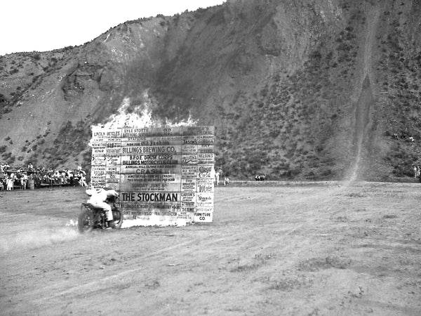 Billings Motorcycle Club stuntman crashing through a flaming barrier at 60 MPH during the first Indian Point hill climb event recognized by the American Motorcycle Association, June 5, 1938. -- Courtesy Fears-Salsbury Collection, Western Heritage Center
