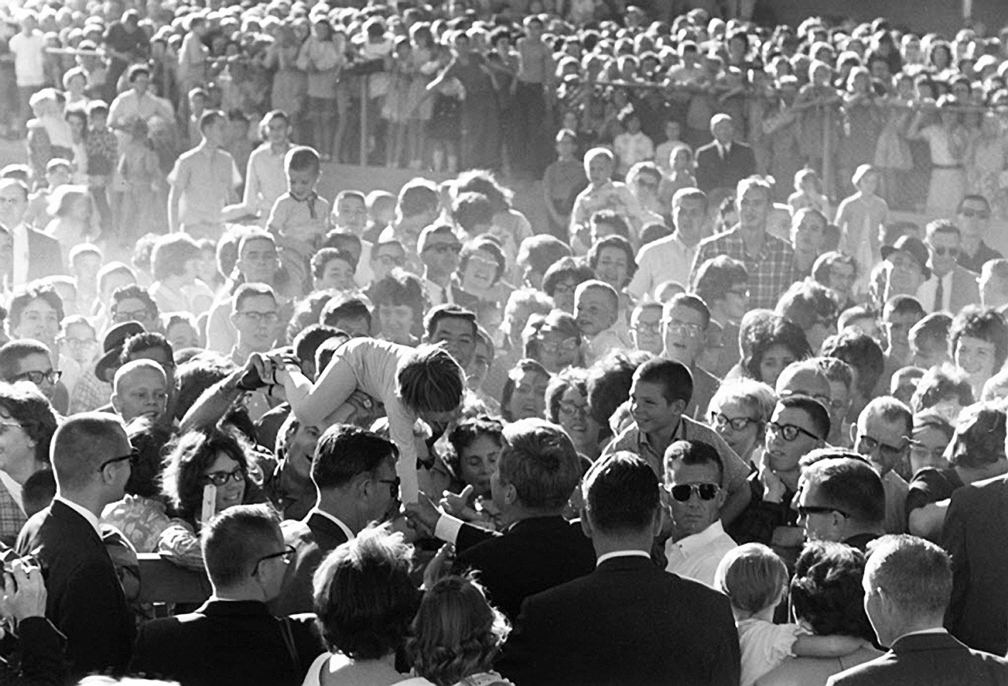 "A young girl is lifted above the crowd to shake hands with President Kennedy during the President's ""Conservation Tour"" of Western States, Billings, September 1963. -- COURTESY CECIL STOUGHTON"