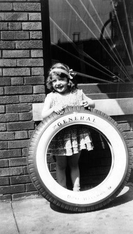 Joyce Anderson with an Anderson Tire outside her dad's store on State Street, 1931. She was a local singing star and often sang for money outside of Ma Bennet's next door. -- Courtesy Brooksy Beilke-Skoug