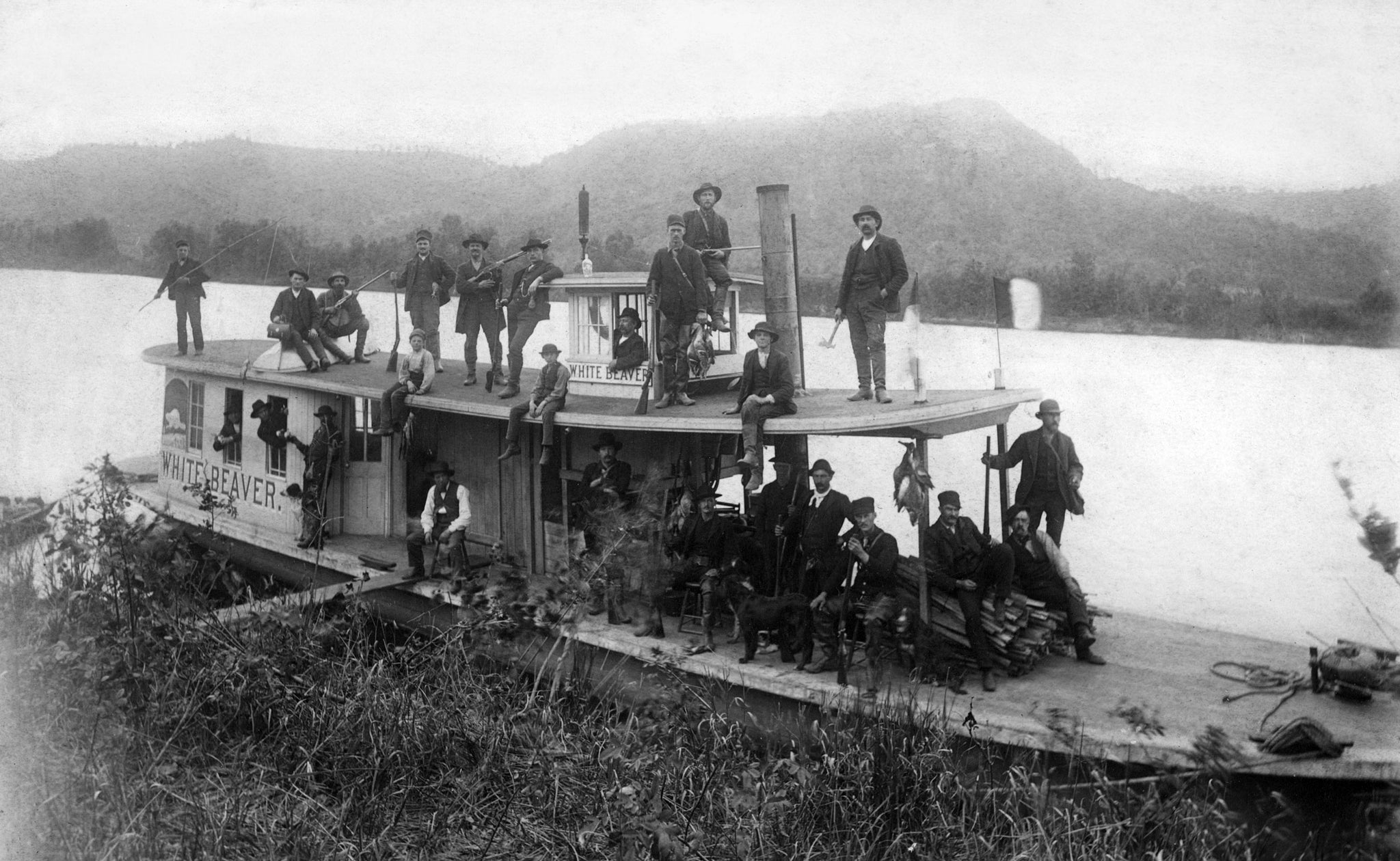 A hunting party on the steamboat White Beaver, circa 1900. The boat belonged to G. L. Winslow, who can be seen sitting on the wood pile. His son, E. M. Winslow, is on the left. -- COURTESY UNIVERSITY OF WISCONSIN-LA CROSSE / #17260