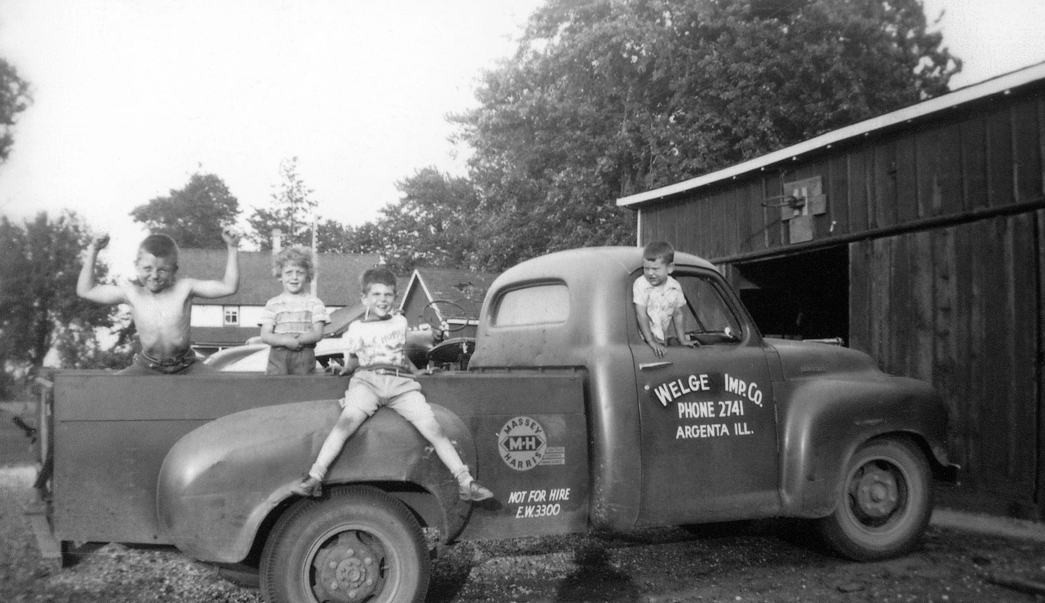 Children playing on the Welge Implement Co. truck in Argenta, circa 1959. -- Courtesy Curt Jackson