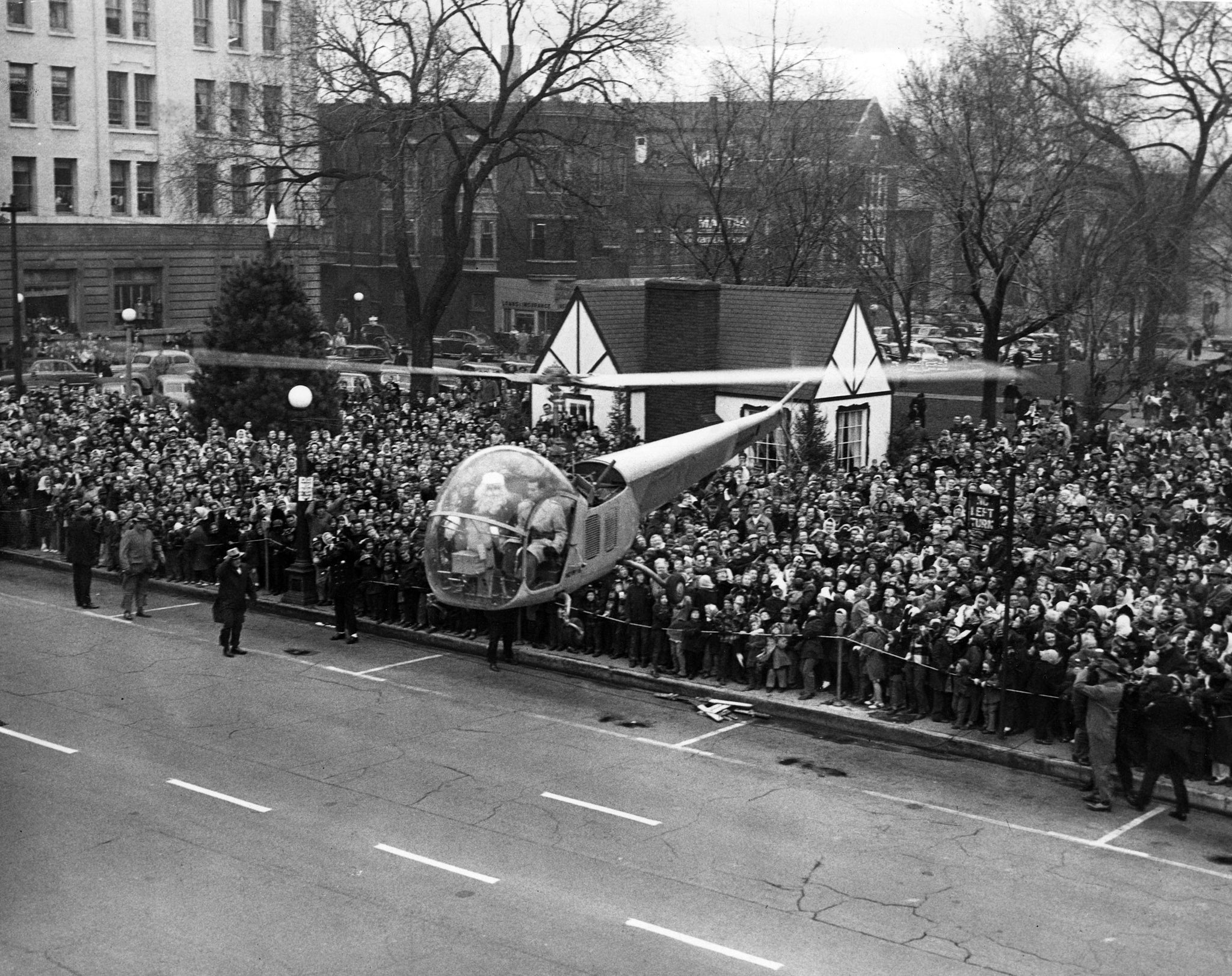 A crowd watching as Santa lands on Water Street in a helicopter, 1949. -- Herald & Review