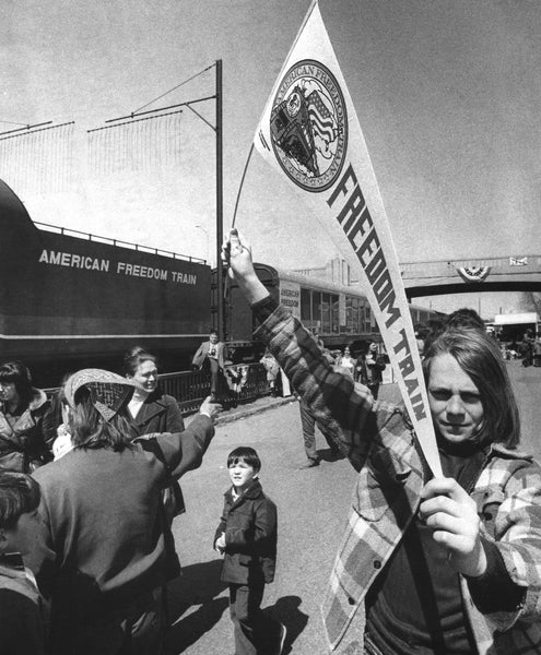 A young Queen City resident proudly displays her American Freedom Train banner on April 15, 1975.  -- Photo by Alan Jahn. Union Leader Archives