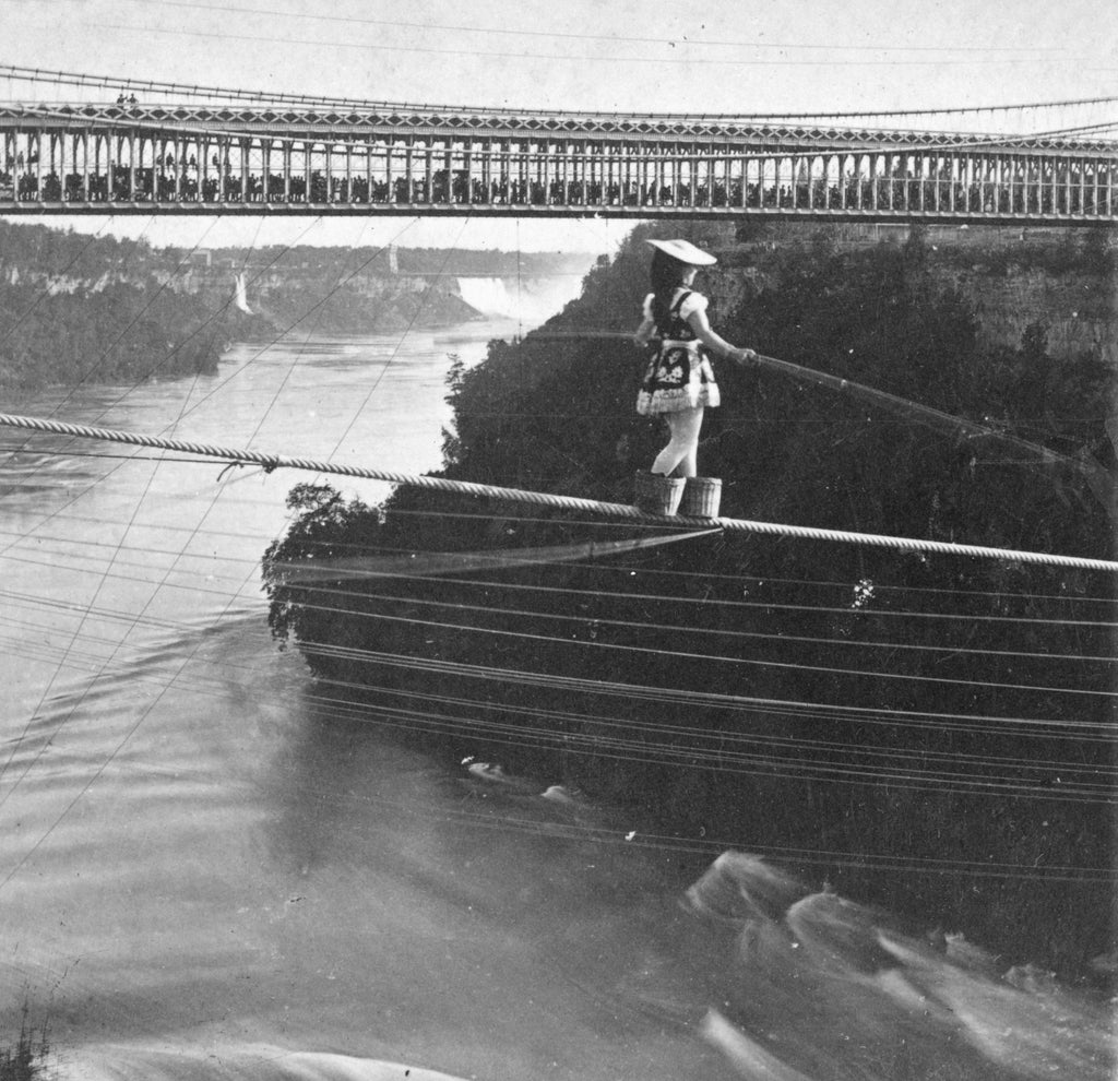 Maria Spelterini crossing Whirlpool Rapids on a high wire with peach baskets on her feet. -- Niagara Falls Public Library