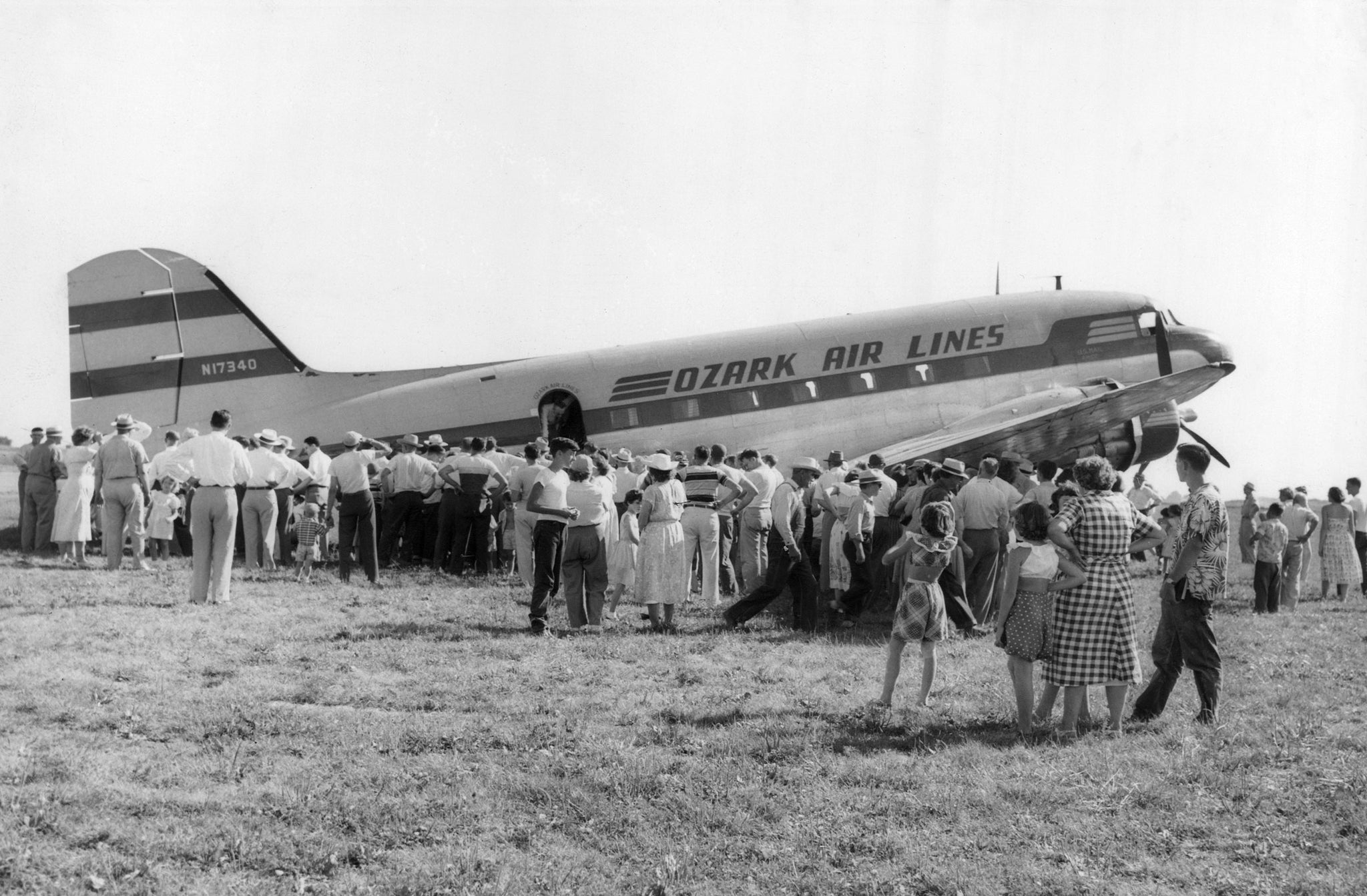 An Ozark DC-3 being inspected by curious citizens on Air Carrier Get Acquainted Day at Municipal Airport, 1951. It was a day where the plane was open to public viewing, and a few lucky citizens took a ride around Bloomington. -- Courtesy of the McLean County Museum of History, Pantagraph Collection