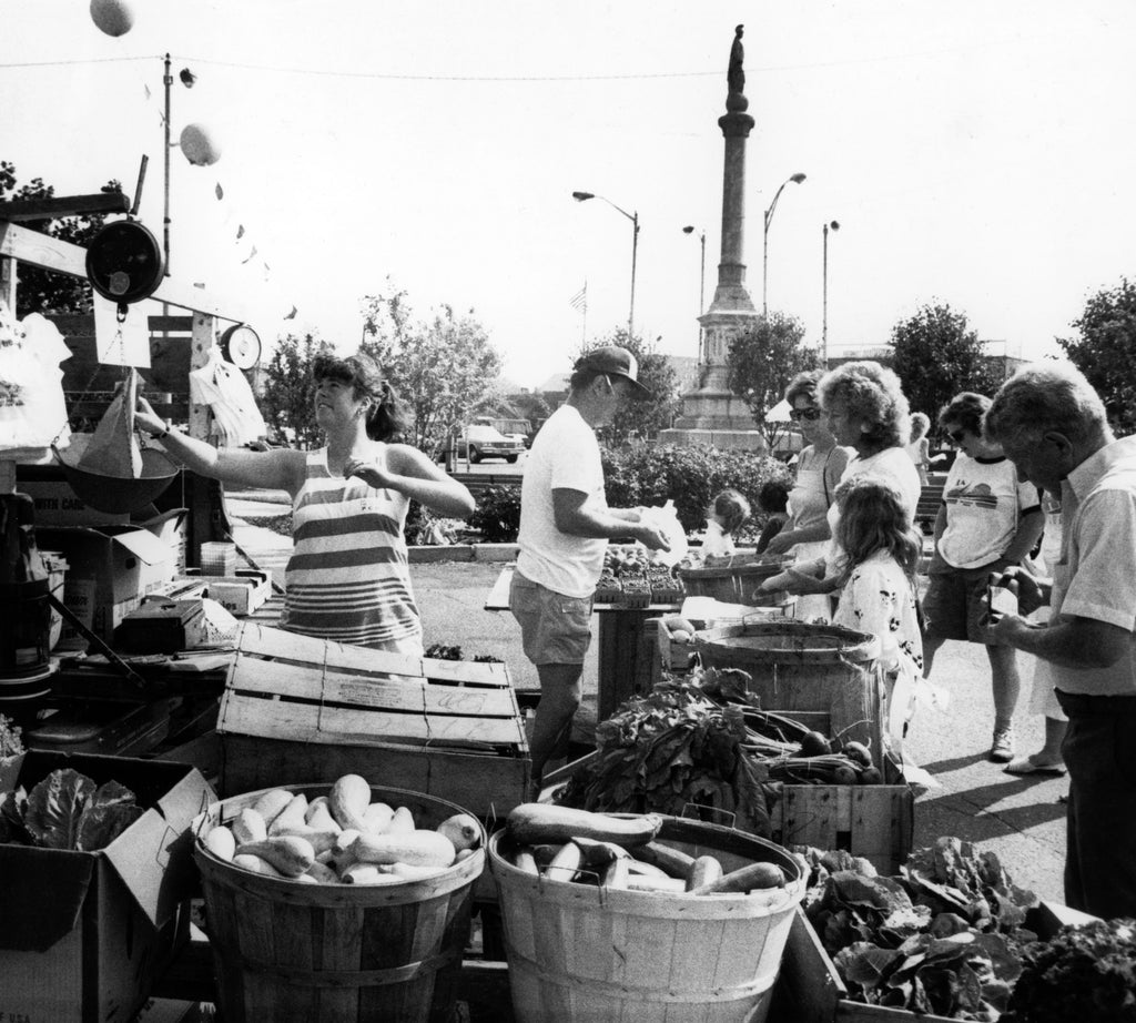 Cathy Haynes, left, is weighing items and Bill Clark is helping customers at the Clark Farm stand at the Peabody Farmers Market in July 1989. -- Courtesy The Salem News
