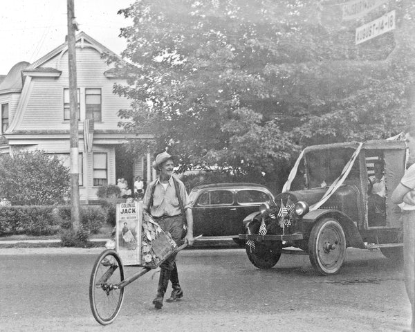 "Celebrating Salisbury's tercentenary (300th) birthday parade, August 14-18, 1938, with celebrity Colonial Jack (John Albert Krohn of Salisbury), pushing his wheelbarrow. Colonial Jack walked 9,024-miles around America and  had to get cancellation stamps from 635 post offices along the way. By the end of his journey, Krohn walked 9,024 miles and visited 1,209 cities. He went through 11 pairs of shoes, 112 pairs of socks and five wheels and three tires on the wheelbarrow. The trip cost an average of $3.25 per day. Krohn, a 35-year-old former newspaperman, relied on his flair for publicity to defray his expenses. He called himself ""Colonial Jack."" His wife traveled ahead arrival and restocked his supply of commemorative tokens. The photo was taken in the Town Common where the Institution for Savings was later erected. -- Knowles Family Collection"