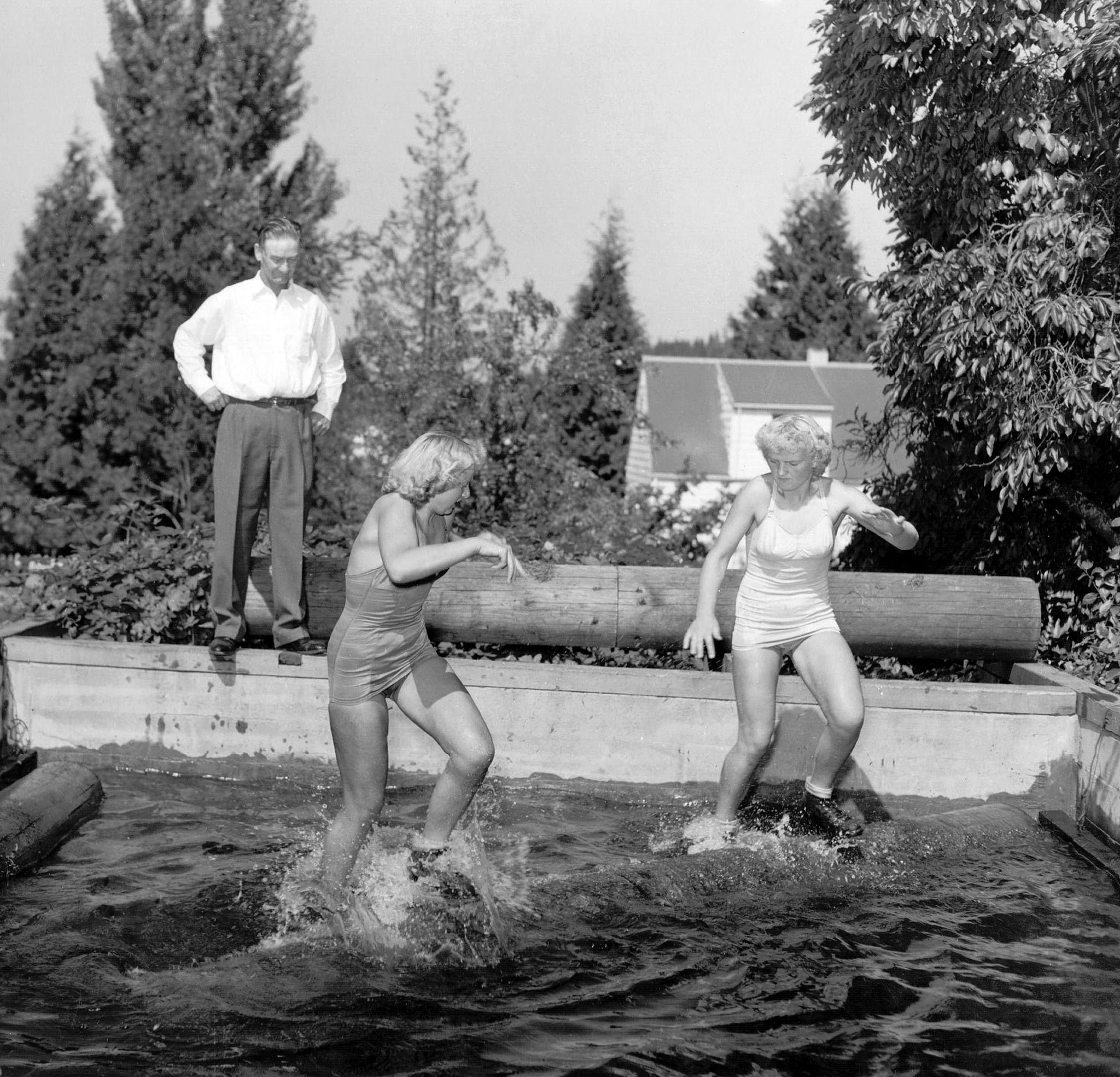 World Champion log rolling sisters Charlotte Hansen (left) and Virginia Hansen (right) practice under the direction of their father, Frank Hansen. The Hansen sisters of Toutle often faced each other as they traveled the country competing and performing at logging shows throughout the 1950s. -- Courtesy Darcy Mitchem