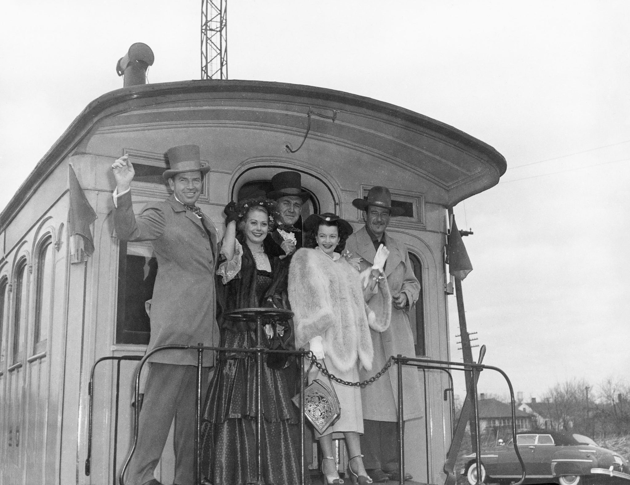 "From left: Forrest Tucker, Adele Mara, Bruce Cabot, Dale Evans and John Wayne wave from the back of a train after the world premier of ""Rock Island Trail"" at three Quad-City movie houses, 1950. -- Rock Island County Historical Society"