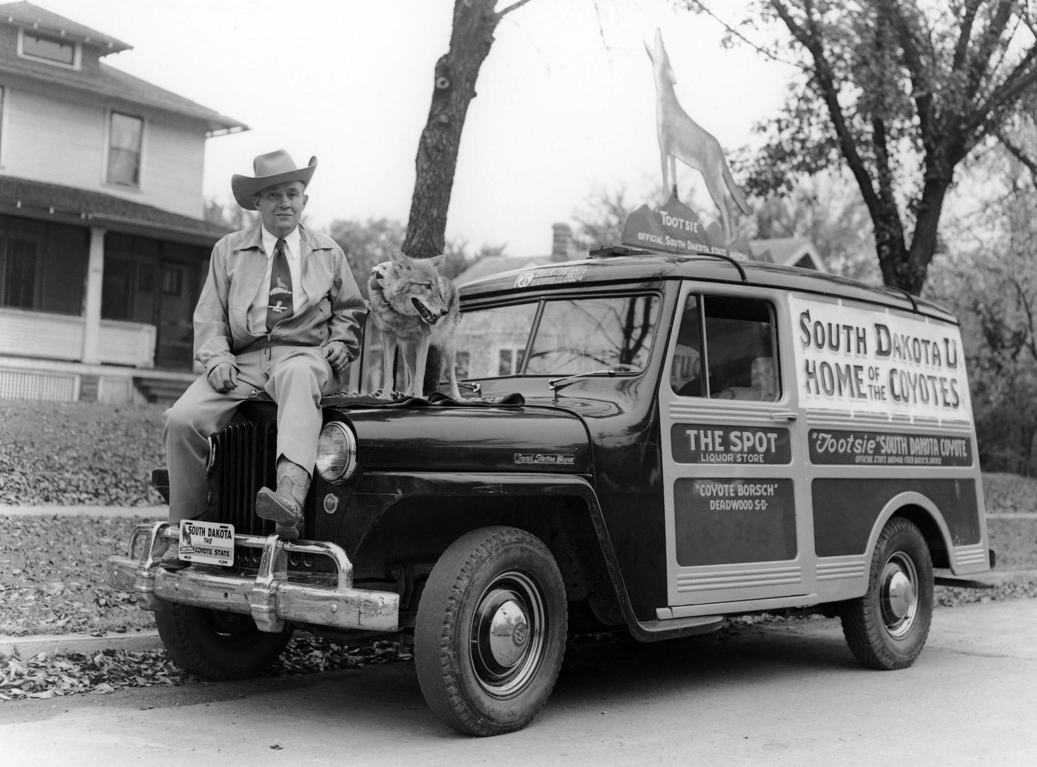 """Coyote"" Fred Borsch and Tootsie the Singing Coyote with the Spot Liquor Store wagon, Deadwood, 1953. Tootsie was dubbed South Dakota's State Animal by Gov. George Mickelson in 1949. -- Courtesy Deadwood History, Inc."