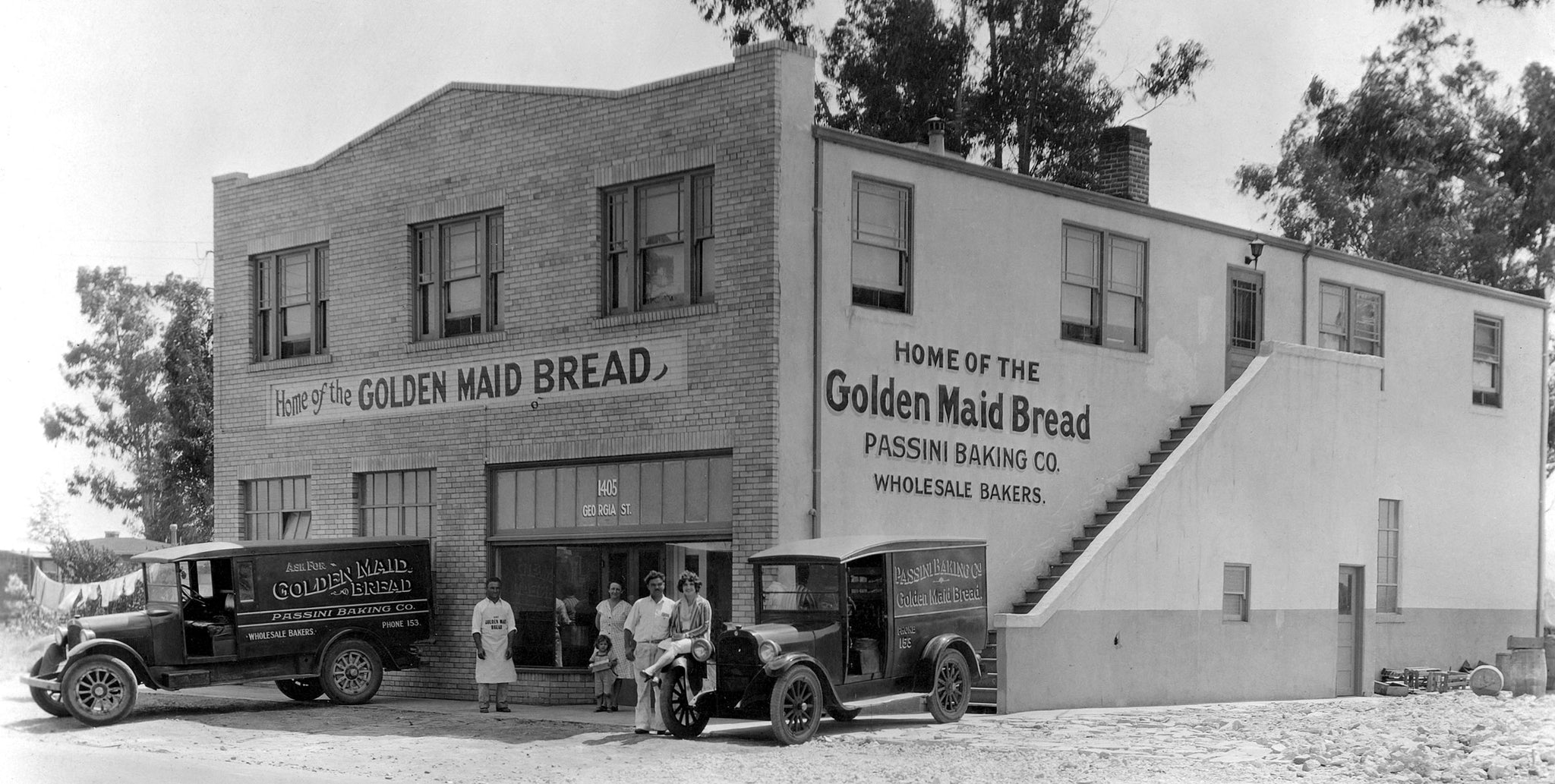 "Passini Bakery, 1405 Georgia Street, circa 1933. The bakery produced Golden Maid Bread and wholesale baked products. The business was at this same location until 1971. On the left is Charles ""Moonie"" Passini. Standing next to the car is Alfonso ""Sunshine"" Passini, Charles's brother and partner. Upstairs were apartments. -- Courtesy Arlene Passini"