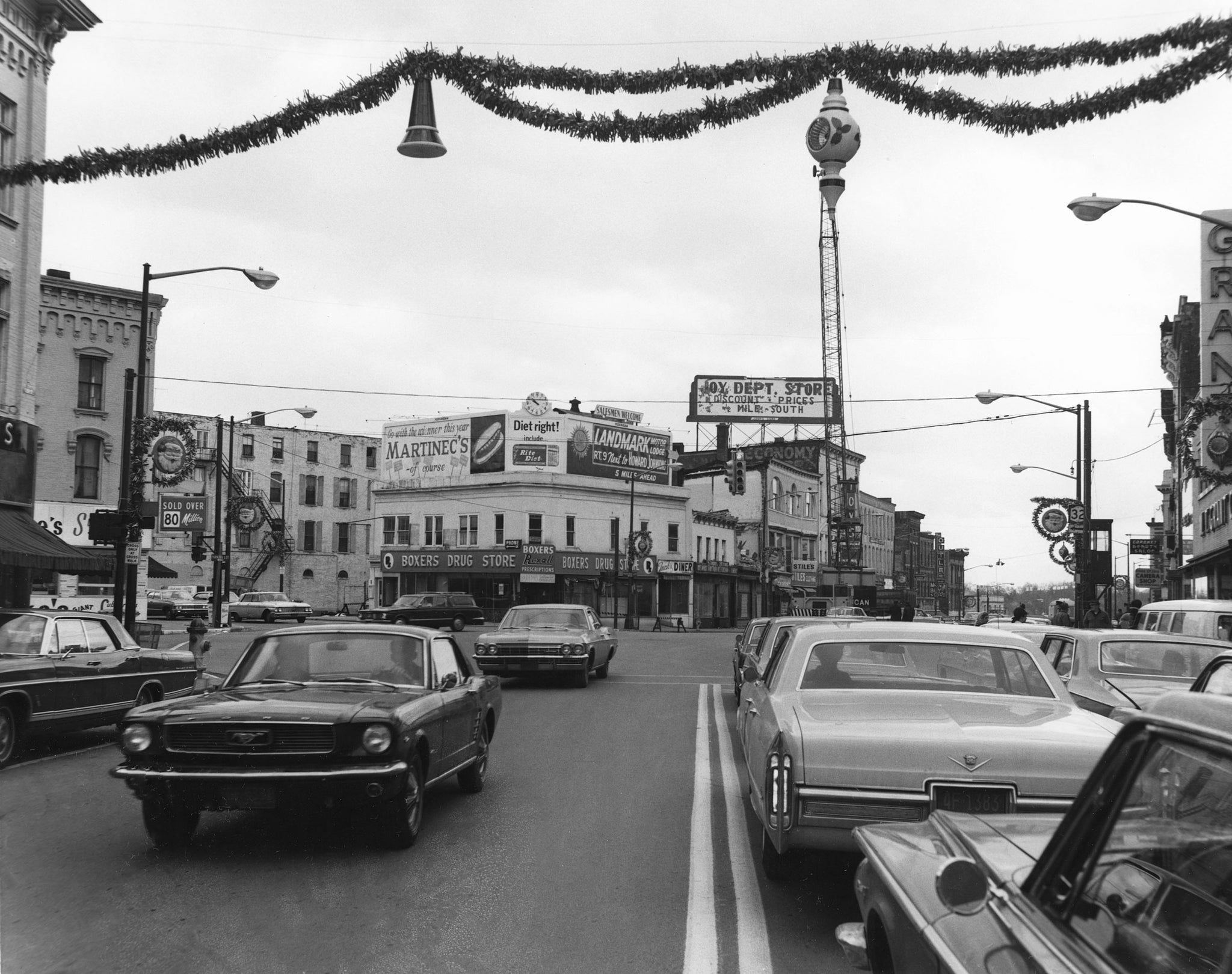 View down Glen Street toward Boxer's Drug Store on the intersection of Glen and Warren Streets, November 1968. Note the Christmas decorations hanging above the street. -- Folklife Center at Crandall Public Library