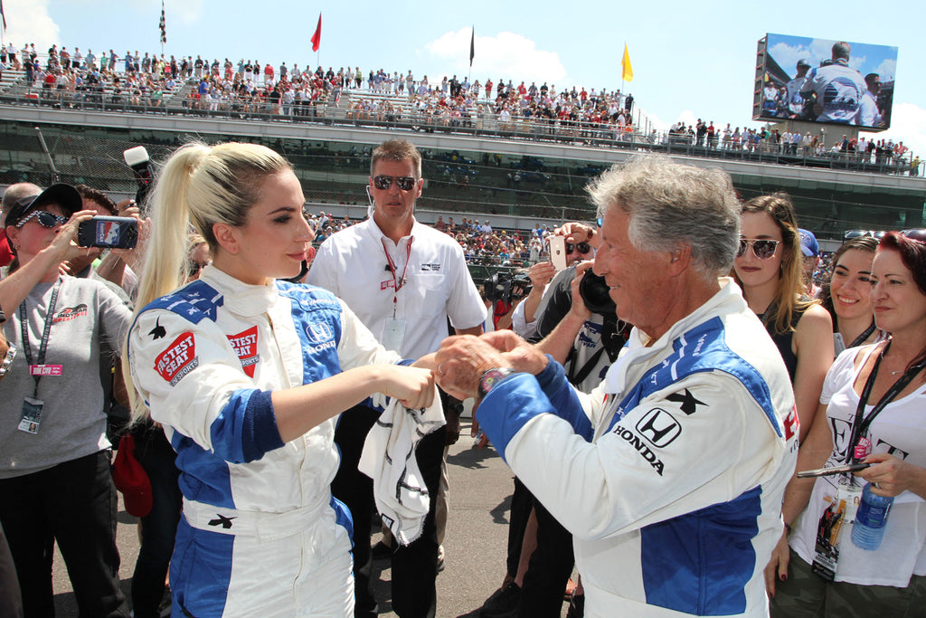 Lady Gaga and Mario Andretti do a double fist-bump before they take a lap in the two-seater IndyCar before the 100th running of the Indianapolis 500, May 29, 2016. -- Kerry Keating/For The Star