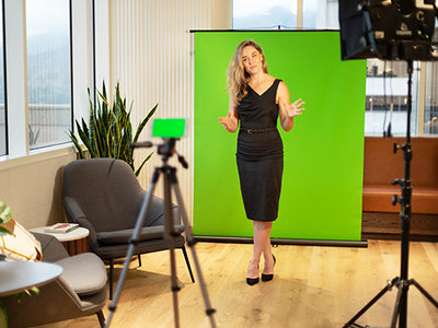 Business person standing in front of Creator 95 green screen shooing a video.
