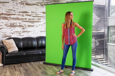 Youtuber standing in front of Creator 95 green screen shooing a video.