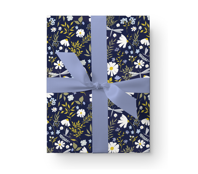 Illustrated wrapping paper gift box with a lovely floral pattern with daisies and dragonflies on a dark navy background.