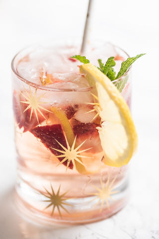 A pink-coloured drink filled to the brim of a short round glass covered in gold starbursts. The drink contains slices of strawberries and lemon and is garnished with a slice of lemon and mint leaves, with a white straw sticking out at the back.]