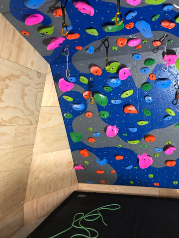plywood climbing wall painted with durabak bed liner dark blue dark grey colorful grips