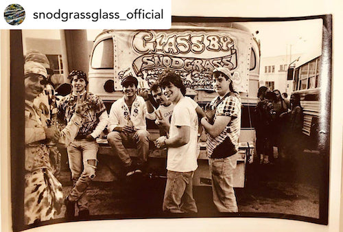 Vintage picture of people, concertgoers or glass enthusiasts, crowding around a bus with a sign that reads Glass by Snodgrass