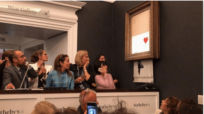 Photo of Banksy's Girl with Dress piece being shredded at Sotheby's auction