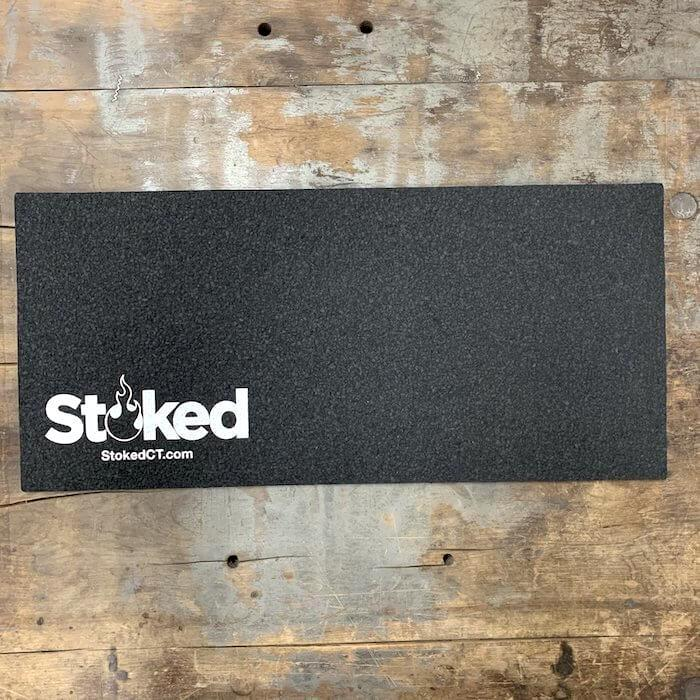 Black mood mat on a wooden background; white Stoked logo in bottom left corner, includes stokedCT.com