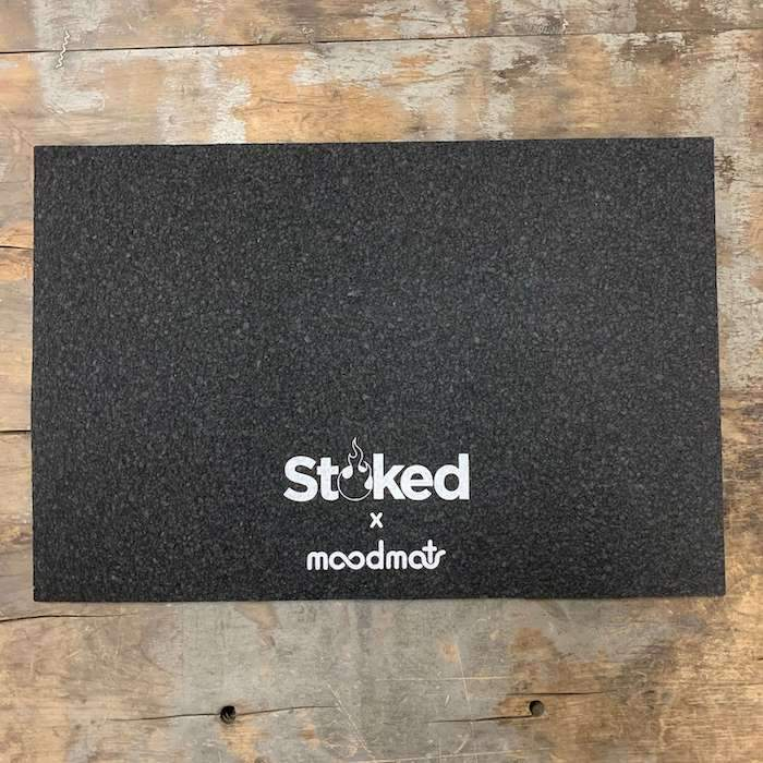 Stoked 12x18 inch mood mat on wood background with Stoked x moodmats logo center bottom