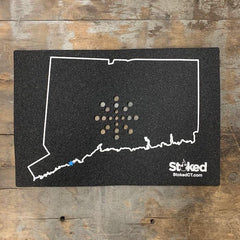 Mood mat on wood background with State of Connecticut outline and stoked logo, bottom right